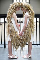 © Licensed to London News Pictures. 27/07/2018. LONDON, UK.  Brazilian artist Tunga's performance featuring twins connected by their hair, is staged at Tate Modern.  The signature work, Xifópagas Capilares entre Nós (Capillary Xiphopagus among Us) reflects the artist's fascination with the uncanny, surreal and inexplicable and features twin adolescent girls appearing unexpectedly and sporadically in the galleries.  Tunga's interest in hair and its 'magical' properties, a recurring symbol across much of his work, can also be seen in Tate Modern's current free display of the artist's work, which features a braid made of lead.  Performance run throughout weekends in July and August.  Photo credit: Stephen Chung/LNP