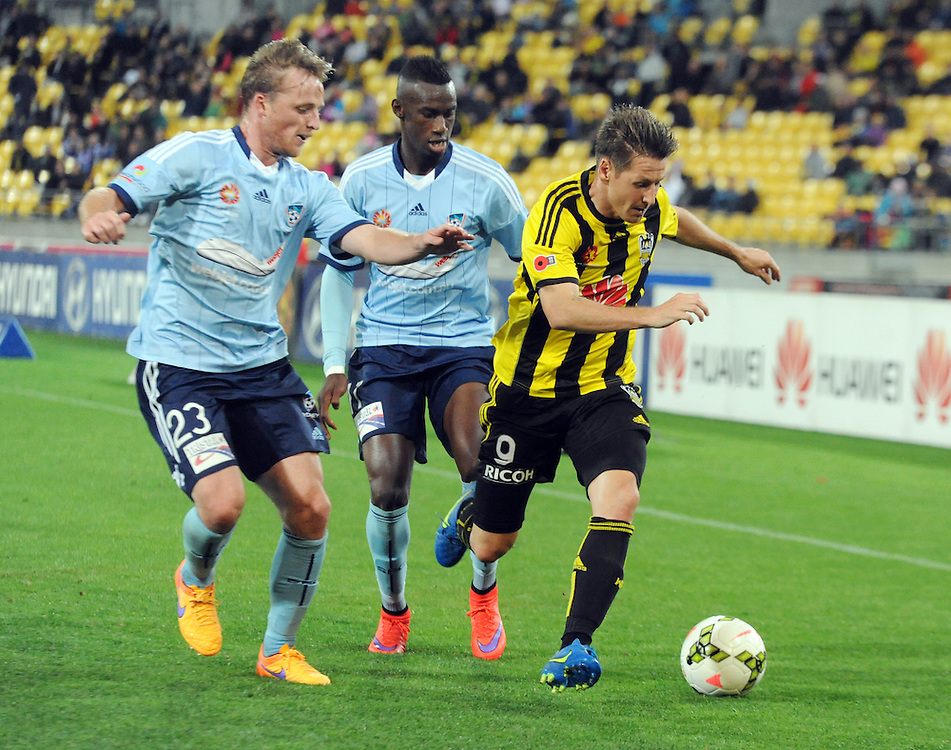 Sydney FC's Rhyan Grant, left and Bernie Ibini-Isei chase down Phoenix's Nathan Burns in the A-League football match at Westpac Stadium, Wellington, New Zealand, Sunday, April 26, 2015. Credit:SNPA / Ross Setford