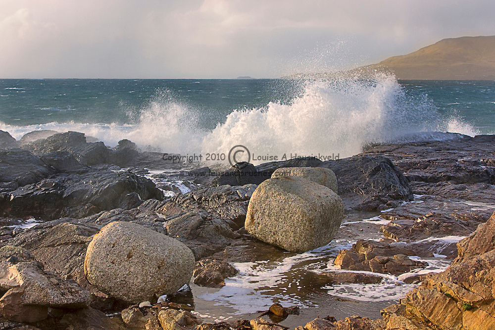 Waves crash on the rocky shoreline of Clew Bay, Murrisk, Ireland, on a stormy day