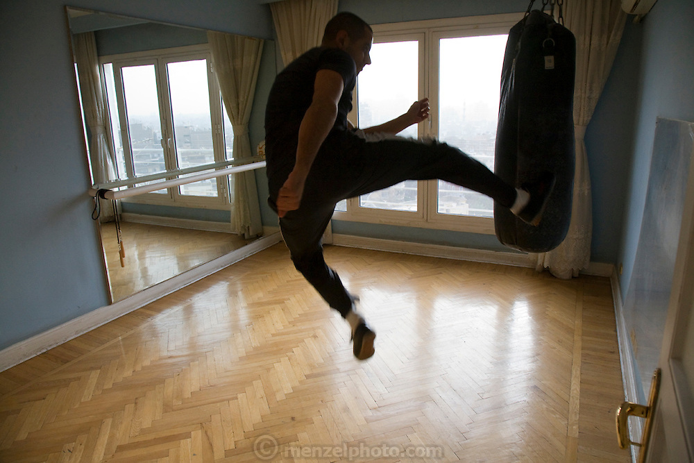 George Bahna, an engineering company executive and martial arts instructor exercising in a special room in his apartment in Zamelek, Cairo, Egypt. (From the book What I Eat: Around the World in 80 Diets.) The caloric value of his day's worth of food on a typical day in the month of April was 4000 kcals.  He is 29 years of age; 5 feet, 11 inches tall; and 165 pounds. George eats four to five times a day but doesn't worry about gaining weight because he's active, working out in a special room in his flat and at the private Gezira Sporting Club near his apartment. MODEL RELEASED.