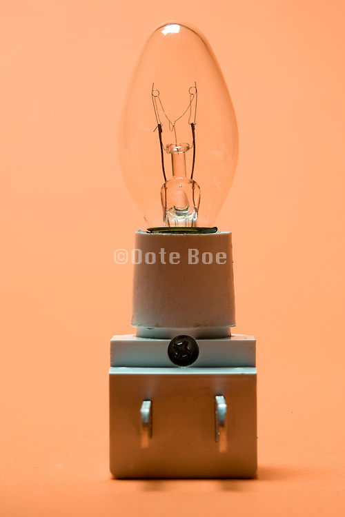 a plug in little night light against an orange background