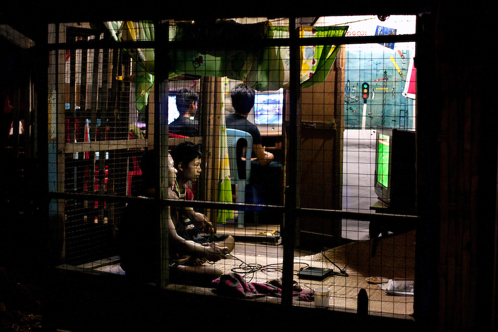 Boys play video games in Dagon Township, Myanmar, Tuesday, May 7, 2013.  After the last election Myanmar is changing rapidly because foreign investment, the country is going into globalization, using mobile phones, internet, buying cars and motorcycles, wearing the same clothes than western countries. There is a lot of hotels even some of them 5 stars with astronomic prices but most of the population still been poor, without drinking water in their houses or health care.