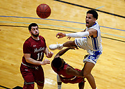 Dakota Wesleyan's Tyson Smiley (11) passes the ball while colliding into Hastings College's Kevin Miller (1) as Tyler Hedlund (11) looks on during a game on Wednesday in the first round of the Great Plains Athletic Conference tournament at the Corn Palace. (Matt Gade / Republic)