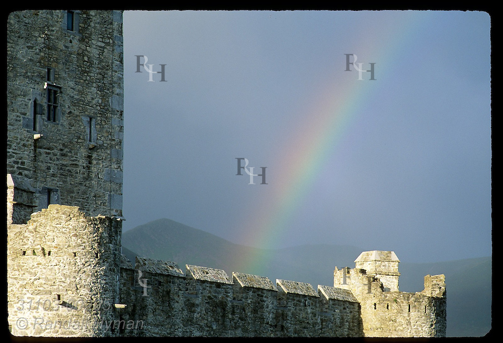 Early morning rainbow glows behind section of 15th-century Ross Castle on Lough Leane in Killarney National Park, Ireland.