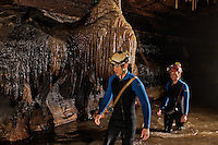 Cavers walking past beautiful flowstone formations in a large watery passage.