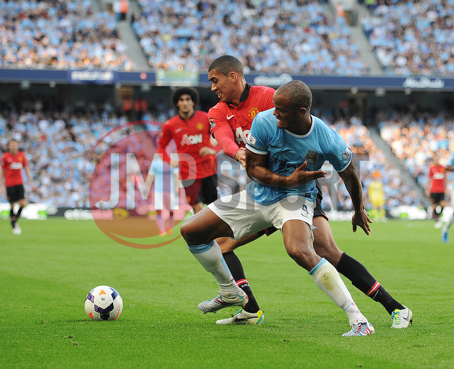 Manchester City's Vincent Kompany and Manchester United's Chris Smalling jostle for the ball - Photo mandatory by-line: Dougie Allward/JMP - Tel: Mobile: 07966 386802 22/09/2013 - SPORT - FOOTBALL - City of Manchester Stadium - Manchester - Manchester City V Manchester United - Barclays Premier League