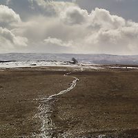 A single winding path across snow-covered moorland