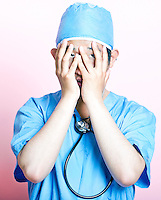 Young Asian surgeon wearing scrubs and looking stressed
