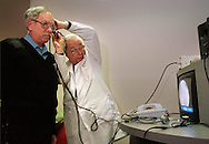 Pete Cyphers, left, has a video camera placed into his ear by Dr. Woodrow B. Kessler, right, at the TDx MacDade Mall Medical Center in Holmes, Pa., Monday, March 21, 1999. The video image of Cyphers' ear, on screen, is then sent via phone line to Kessler's Wallingford, Pa., office where his son Dr. Rex Kessler, not shown, views the image to consult on the examination. Woodrow says the technology he is using is invaluable to doctors looking for consults on patients all over the world.   (photo by William Thomas Cain)
