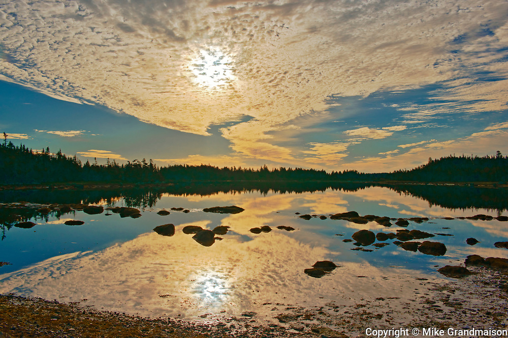 Reflection of clouds in rocky pond, Harrigan Cove, Nova Scotia, Canada