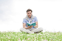 Portrait of young man reading book while sitting on grass against sky