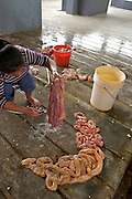 A WOMAN WORKING IN THE SLAUGHTERHOUSE IS PREPARING THE INTESTINES OF THE SACRIFICED ANIMALS TO SELL THEM LATER IN THE LOCAL MARKET.