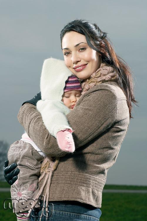 Mother hugging sleeping baby
