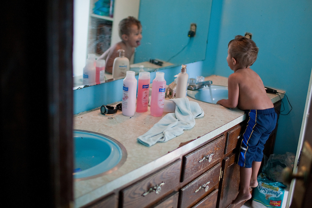 Jojo washes his hand in the bathroom and check his reflection in the mirror.