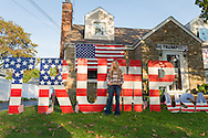 "Bellmore, New York, USA. November 2, 2016. EILEEN FUSCALDO, a Donald Trump Supporter, stands in front of TRUMP display, one of many in her front yard Halloween display for the Republican presidential candidate, D. J. Trump, and against Democratic one, H. R. Clinton.  On her front door is a life-size cardboard Trump holding ""The Silent Majority Stands with Trump"" sign."
