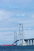 Oil tanker passes under The Great Belt Bridge suspension bridge over Storebaelt view from Halskov, Denmark