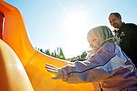 Jayden Holt, 4, tries to climb up a slide as her father, Charles Holt, encourages her during a sunny day outing Tuesday at Cherry Hill Park in Coeur d'Alene.