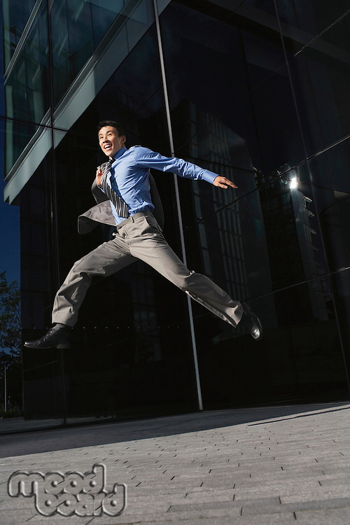 Businessman jacket over shoulder Jumping outside building