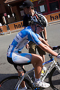 A member of the Horizon Fitness womens' road racing cycling team waits to re-join the Woking street race after bike repairs/
