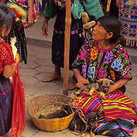 Central America, Latin America, Guatemala, Chichicastenango. Young girl stands by watching puppies for sale in the Chichicastenango market.