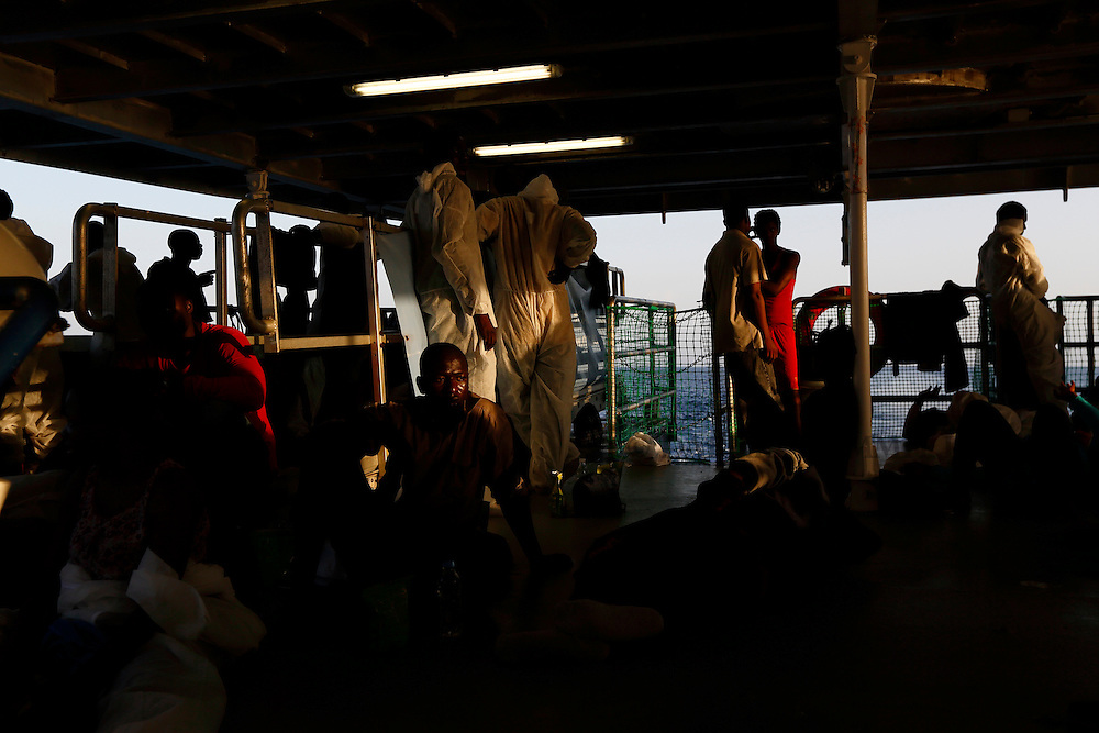 Rescued migrants rest on the deck of the Migrant Offshore Aid Station (MOAS) ship MV Phoenix between Libya and the Italian island of Lampedusa, August 3, 2015.  118 migrants were rescued by the Phoenix from a rubber dinghy some 20 miles (32 kilometres) off the coast of Libya on Monday morning. The Phoenix, manned by personnel from international non-governmental organisations Medecins san Frontiere (MSF) and MOAS, is the first privately funded vessel to operate in the Mediterranean.<br /> REUTERS/Darrin Zammit Lupi <br /> MALTA OUT. NO COMMERCIAL OR EDITORIAL SALES IN MALTA