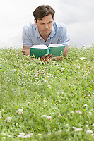 Man reading book while lying on grass against sky