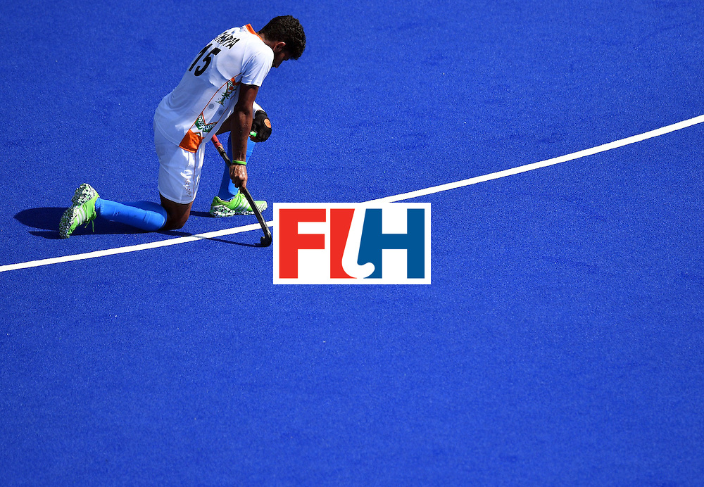 TOPSHOT - India's Uthappa Sannuvanda kneels on the pitch at the end of the men's quarterfinal field hockey Belgium vs India match of the Rio 2016 Olympics Games at the Olympic Hockey Centre in Rio de Janeiro on August 14, 2016. / AFP / Carl DE SOUZA        (Photo credit should read CARL DE SOUZA/AFP/Getty Images)