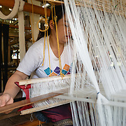 Woman weaving on a machine in Luang Prabang