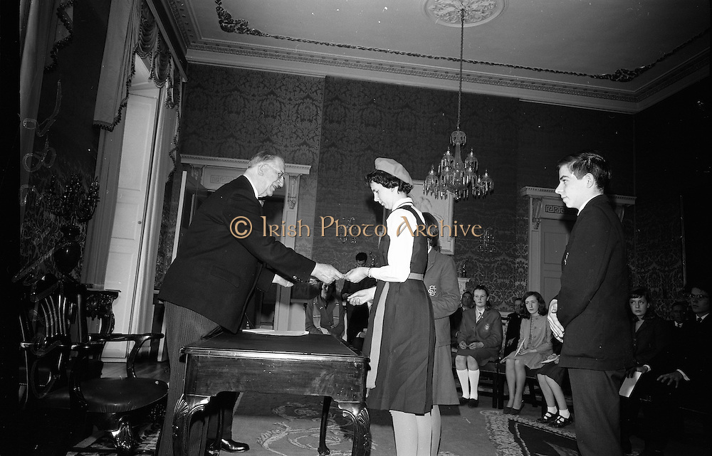 """28/04/1966<br /> 04/28/1966<br /> 28 April 1966<br /> President Eamon de Valera presents prizes at Aras an Uachtarain. The President presented the prizes to the winners of competitions for schoolchildren organised by the Golden Jubilee 1916 Committee. The winners from schools all over Ireland competed in competitions for essays and poetry in Irish and English. Picture shows President de Valera presenting a joint 2nd prize for Essay in English to Caitlin Ní Fhingealtúin, Baile an Gharraí, Durlas Eile, Co. Thiobraid Arann, appeal of Clochar na Toirbhirte. Other receivers were Clara Ní Chonghaile, 8 Sraid Oilibhéar Pluincéad, Loch Garman and Cathal Brugha, """"Ceann Slé"""", 30 Bothar an Ruaphoic, Dun Droma, Baile Atha Cliath of Colaiste Gonzaga."""