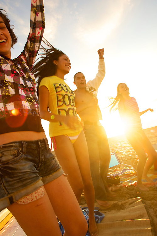Summer dance beach party with a group of tweens with sunset backlighting the gropup as they dance together
