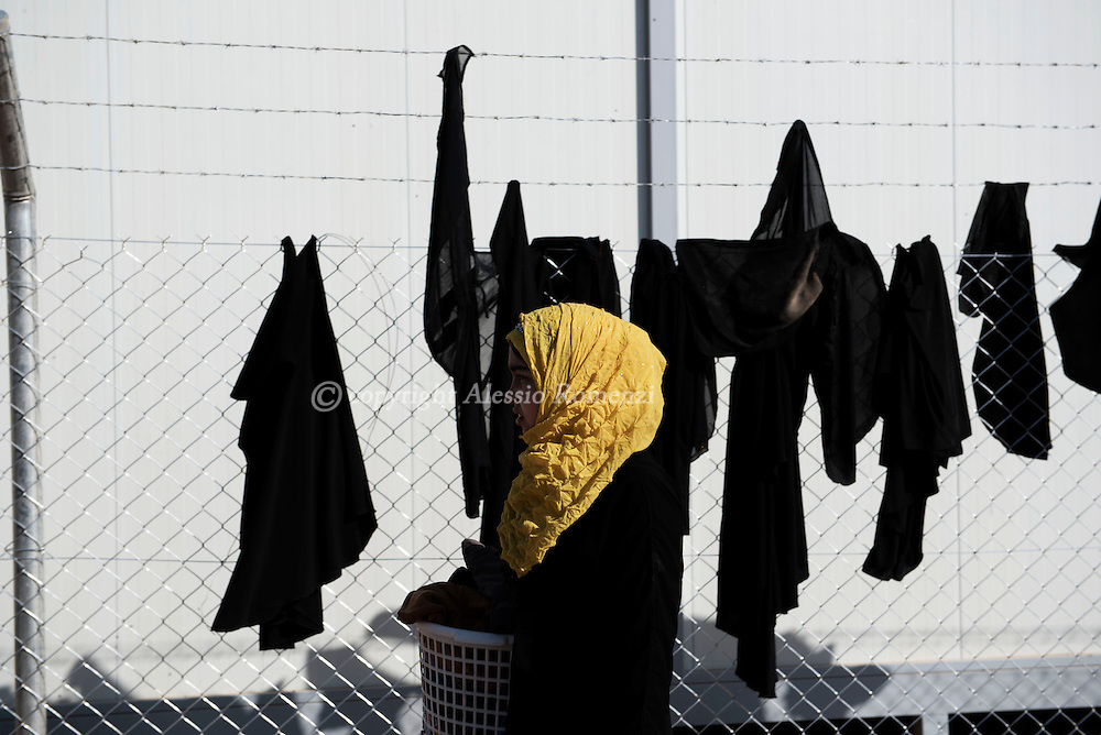 Iraq: Civilians line up as they arrive by truck at the entrance of the Hasan Shame IDP camp in Al Kazir area after fleeing fighting in Mosul on November 5, 2016. <br /> The black clothes on the backdrop are black veils that woman take off not being obliged anymore by ISIS. Alessio Romenzi