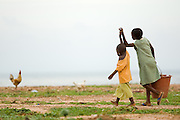 Two girls hold hands while they carry a bucket in Accra, Ghana on Tuesday June 16, 2009.