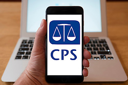 Using iPhone smartphone to display logo of Crown Prosecution Service, in the UK
