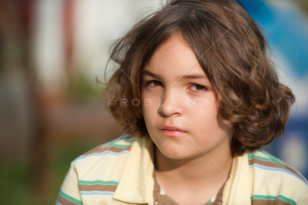 Young boy with long hair looking at camera