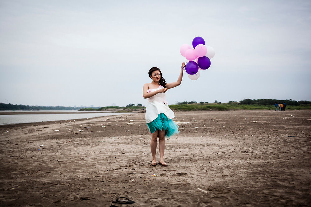 "Nguyen Tuyet Van, a young bride in Hanoi, Vietnam, holds a bunch of colored balloons aloft along the banks of the Red River. Despite heavy winds, grey skies, and chilly weather, many young couples still make their way to the banks of the river to have pre-wedding photographs taken at such a ""romantic"" location. Traditionally (?!) the wedding photographers will touch up such images to create an atmosphere of a beach paradise, where the bride and groom are strolling along white sand beaches under blue cloudless skies. A far cry from the reality of the situation."