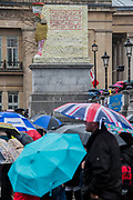 The crowd takes cover from the rain under the watchful eye of the new Fourth Plinth Sculpture  - The Wintershall Players open-air re-enactment of 'The Passion of Jesus' on Good Friday in the rain in Trafalgar Square. It featured a cast of over 100 volunteers from in and around London.