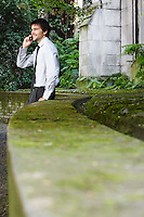 Businessman on cell phone leaning against wall in park
