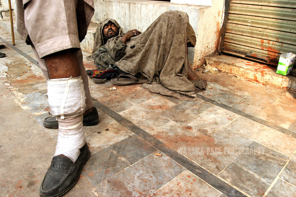 A heroin user shows off his bandaged leg where an abscess developed due to excessive injecting, while another user wakes on the sidewalk covered with flies and a filthy blanket after sleeping in the street, December 11, 2004, Lahore, Pakistan. Heroin is cheap and readily available in Pakistan due to it's proximity to Afghanistan which supplies almost 90% of heroin to Europe. Almost 20% of heroin produced in Afghanistan is trafficked through Pakistan according to the UN Office on Drugs and Crime (UNODC). With the fall of the Taliban, opium cultivation has risen dramatically in spite of Afghan and coalition forces attempts to stem production. Pakistan has between 3.5-4 million heroin users, one of the highest numbers of heroin users in the world, next to Iran. (Photo by Warrick Page)