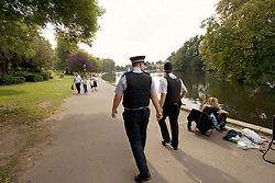 Community Police Support Officer and Police Officer patrolling lakeside area of Raphael Park Havering London UK