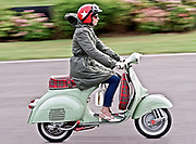 A mod girl, wearing a red helmet, riding her scooter on the street, UK, 2010