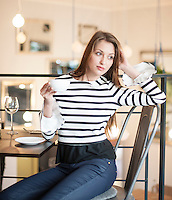 Thoughtful young woman looking away while having coffee at cafe