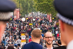 "London, August 24th 2014. Police keep an eye on the teeming Ladbroke Grove as thousands of Londoners of all races and cultures attend Notting Hill Carnival's ""Family friendly"" day ahead of the main carnival on August Bank Holiday Monday."