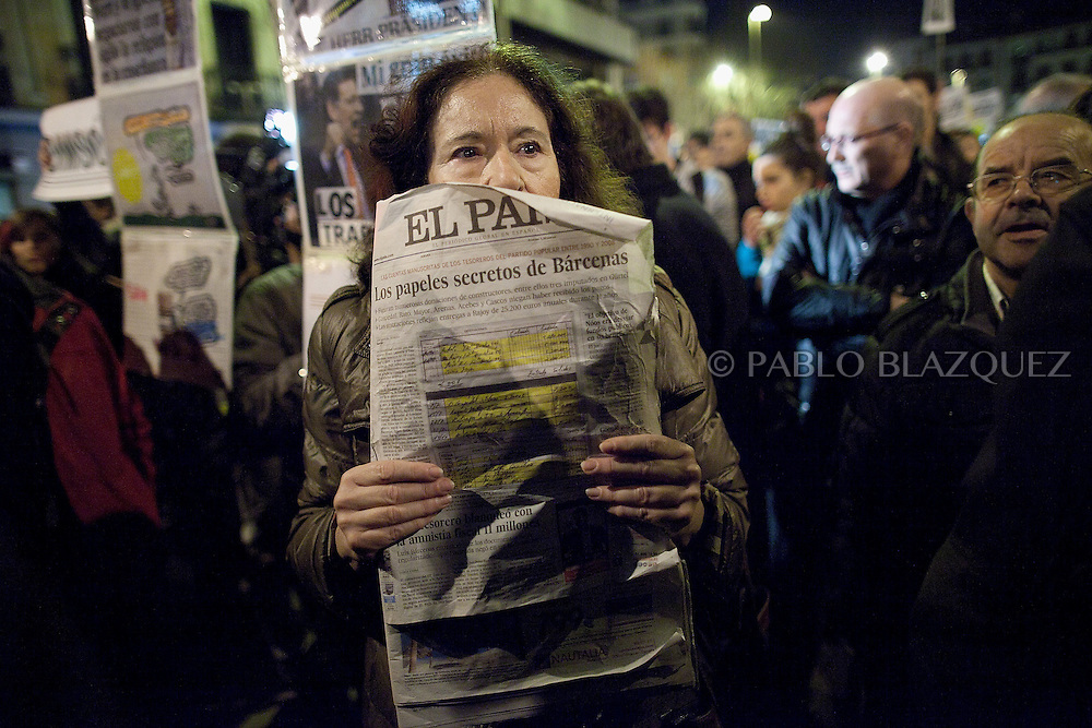 A protester holds a 'El Pais' newspaper during a demonstration against political corruption and claiming Mariano Rajoy to resign outside the PP headquarters in Madrid on January 31, 2013. The Spanish Newspaper 'El Pais' published secret papers of income implicating Spanish Prime Minister and other members of the PP (Popular Party). Rajoy's government has denied these secret payments.