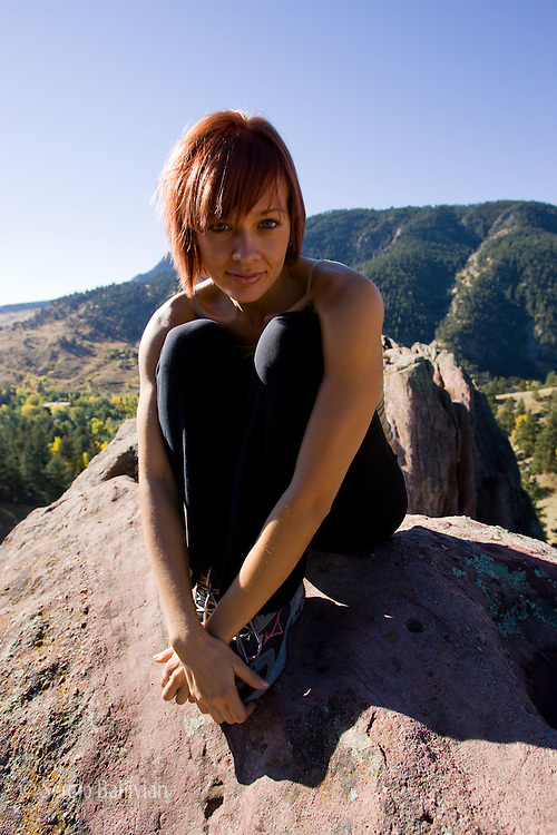 A young woman sits on a rock cliff and enjoys the warm sun on her face and body.