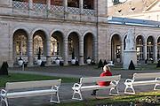 Frau auf Parkbank vor dem Regentenbau, Bad Kissingen, Franken, Bayern, Deutschland