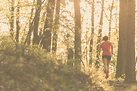 Woman wearing red trail running in early morning light in Blue Ridge Mountains