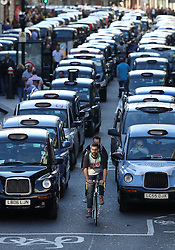 © Licensed to London News Pictures. 30/09/2015. London, UK. Cyclists pass through rows of black cabs blocking Fleet Street in protest over the Uber taxi app. Photo credit: Peter Macdiarmid/LNP