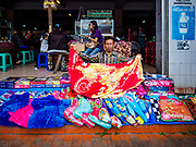 06 AUGUST 2017 - MENGWI, BALI, INDONESIA: A man sets out bed covers he's selling in the Bringkit Market in Mengwi, about 30 minutes from Denpasar. Bringkit Market is famous on Bali for its Sunday livestock and poultry market. Hundreds of the small Bali cows are bought and sold there every week. Bali's local markets are open on an every three day rotating schedule because venders travel from town to town. Before modern refrigeration and convenience stores became common place on Bali, markets were thriving community gatherings. Fewer people shop at markets now as more and more consumers go to convenience stores and more families have refrigerators.     PHOTO BY JACK KURTZ