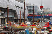 UK, London, Canary Wharf, September 2014.<br /> Docklands Light railway trains passing the Crossrail construction site on the Canary Wharf estate.  Canary Wharf will be one of the largest Crossrail stations. Like the nearby Canary Wharf Tube station, the new Crossrail station will be built in the dock water area, in this case the North Dock of West India Quay. The station and proposed retail and park areas will be six storeys high; approximately the size of One Canada Square laid on its side.