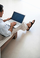 Man using laptop sitting on sofa in living room elevated view
